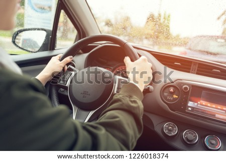 Woman's hands in a green shirt holding the steering wheel of car that rides along the road overlooking the blurry road #1226018374