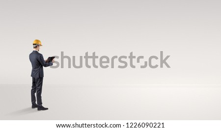 Young architect with construction helmet standing in an empty space and holding a plan #1226090221