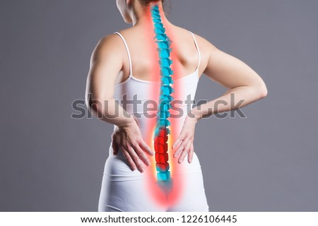 Pain in the spine, woman with backache on gray background, back injury, photo with highlighted skeleton #1226106445