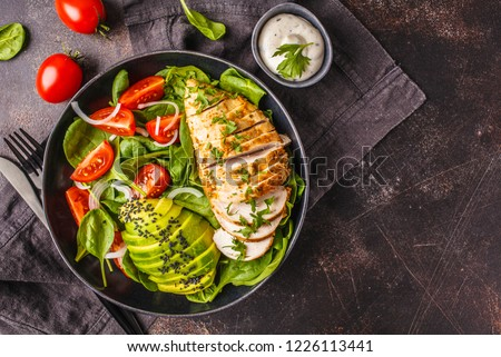Grilled chicken breast and avocado salad with spinach, tomatoes and Caesar dressing in black plate, dark background. #1226113441