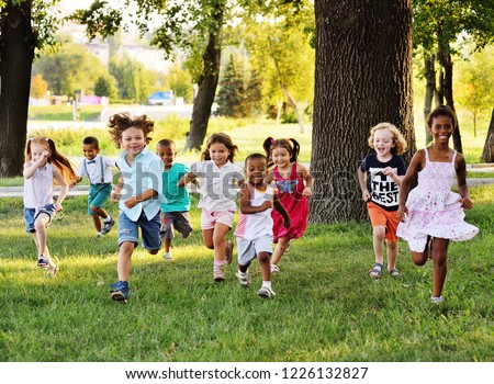 A group of happy children of boys and girls run in the Park on the grass on a Sunny summer day . The concept of ethnic friendship, peace, kindness, childhood. #1226132827