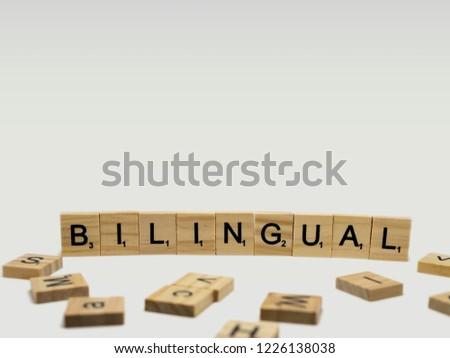"Udonthani, Thailand - November 10 2018: Scrabble tiles spelling ""Bilingual"" on white background #1226138038"