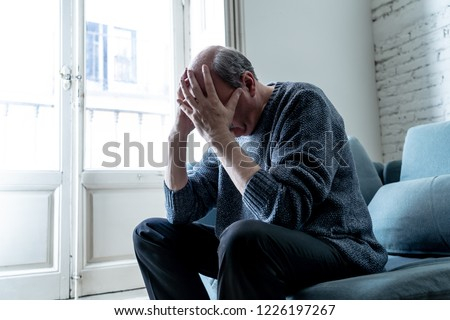 Overwhelmed old senior man suffering alone at home feeling confused sad alone on couch at home in Aging Retirement widower Dementia and Alzheimer concept. #1226197267
