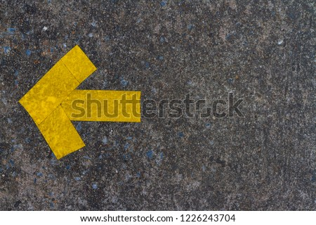 D.I.Y. yellow arrow symbol builds by pike leak seal tape shown on old concrete floor of the walk way. Textured background and copy space.