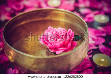 Tibetan singing bowl with floating in water lily inside. Special sticks, burning candles, lily flowers and petals on the black wooden background. Meditation and Relax. Exotic massage. Selective focus #1226282800