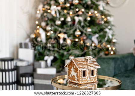 Gingerbread house on table. Defocused lights of Christmas tree. Morning in the bright living room. Holiday mood. Figure deer #1226327305