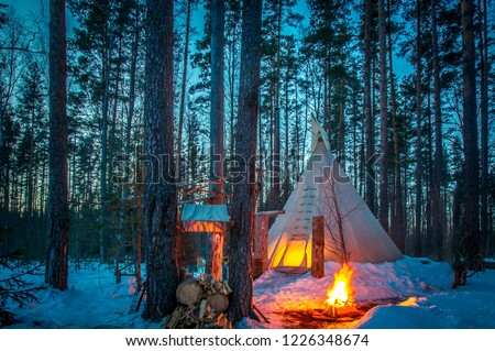 TIPI. Winter. Tipi stands in the winter forest. Bonfire in the forest. Eco-friendly tourism. National dwellings. National Indian dwellings.