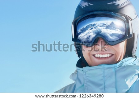 Close up of the ski goggles of a man with the reflection of snowed mountains.  A mountain range reflected in the ski mask.  Portrait of man at the ski resort.  Wearing ski glasses. Winter Sports.  #1226349280