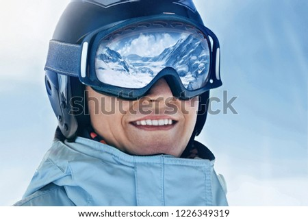 Close up of the ski goggles of a man with the reflection of snowed mountains.  A mountain range reflected in the ski mask.  Portrait of man at the ski resort on the background of mountains and sky #1226349319