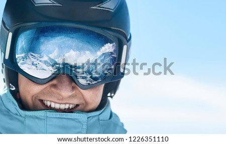 Close up of the ski goggles of a man with the reflection of snowed mountains.  A mountain range reflected in the ski mask.  Man  on the background blue sky. Wearing ski glasses. Winter Sports.  #1226351110
