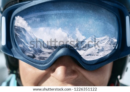 Close up of the ski goggles of a man with the reflection of snowed mountains.  A mountain range reflected in the ski mask.  Man  on the background blue sky. Wearing ski glasses. Winter Sports.  #1226351122