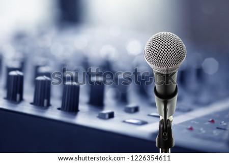 Close up microphone on blur digital audio mixer knops in recording studio with bokeh light background. Microphone on blur audio mixer board in recording studio.