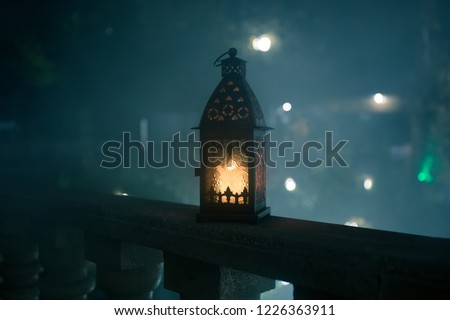 Retro style lantern at night. Beautiful colorful illuminated lamp at the balcony in the garden. Selective focus #1226363911