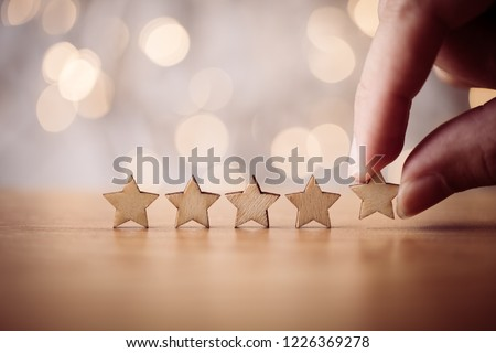 Hand putting wooden five star shape on table. The best excellent business services rating customer experience concept. Royalty-Free Stock Photo #1226369278