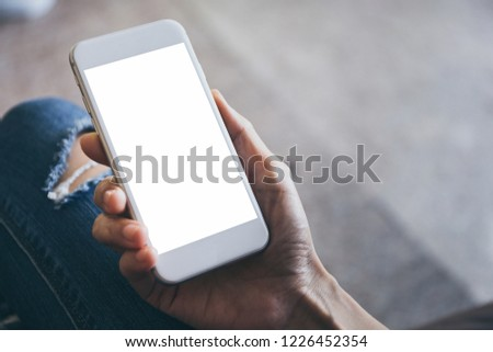 mockup image.woman hand holding texting white cell phone at workplace with concept for electric,communication device research world international modern business,techonology #1226452354