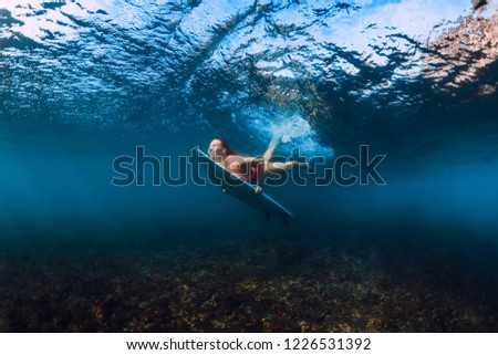 Sporty surfer woman dive underwater with under wave. #1226531392