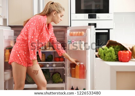 Beautiful young woman choosing food in refrigerator at home #1226533480