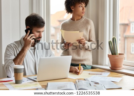 Shot of serious male notes information during phone conversation, tries to remember all instructions from boss, his colleague stands near window, work at workplace at research project, collaborate #1226535538