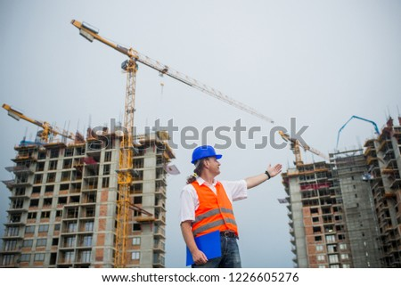 Architect showing buildings on a construction site during a housing project #1226605276
