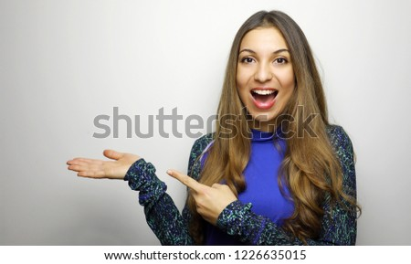 Young sporty girl showing and pointing finger at white background with copy space. Happy beautiful girl shows your product on her hand. #1226635015