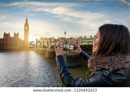Pretty, young London tourist is taking photos with her cellphone from the Big Ben at Westminster during sunset time #1226642623