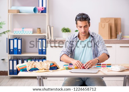 Young handsome tailor working in his workshop #1226658712