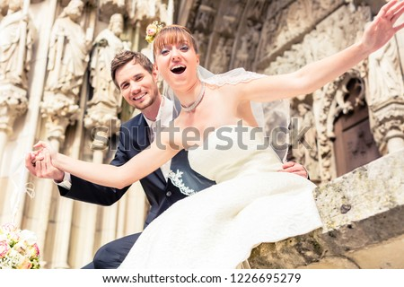 Close-up of excited married couple posing in front of ancient church #1226695279