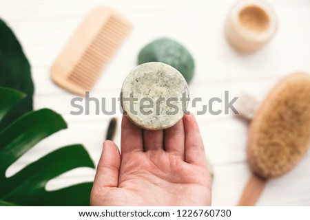 Hand holding natural solid shampoo bar on background of bamboo brush, deodorant, sponge on white wood with green monstera leaves. Zero waste. Choice plastic free eco products Royalty-Free Stock Photo #1226760730