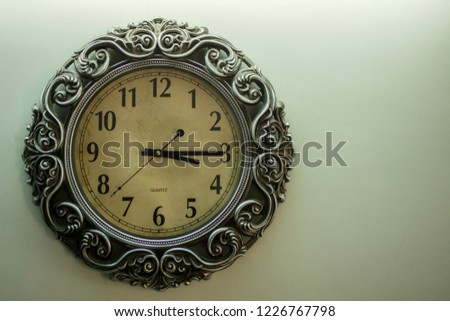 Isolated Ancient Designer Wall Clock With Light Yellow Back Ground showing time 03.15 o'clock and free space on right side soft focus. #1226767798
