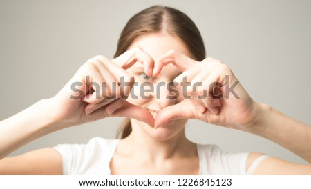 Portrait of smiling young woman with heart shape hand sign #1226845123