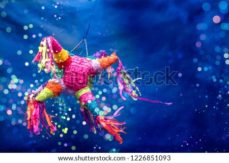mexican piñata party hanging on blue and green background with multi-colored glitters celebrating birthday, christmas, party, party songs, figure in the shape of star and donkey, family fun #1226851093