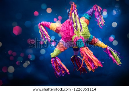 mexican piñata party hanging on blue and green background with multi-colored glitters celebrating birthday, christmas, party, party songs, figure in the shape of star and donkey, family fun #1226851114