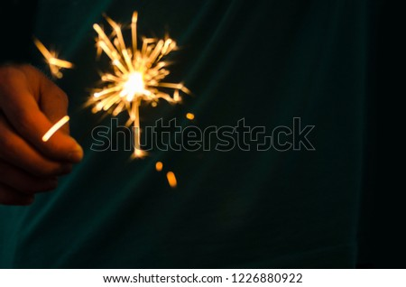 Sparkler fire in hand on black isolated background #1226880922