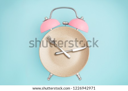 Alarm clock and plate with cutlery . Concept of intermittent fasting, lunchtime, diet and weight loss #1226942971