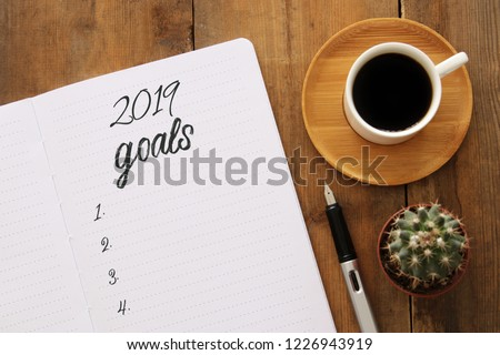 Top view 2019 goals list with notebook, cup of coffee over wooden desk #1226943919