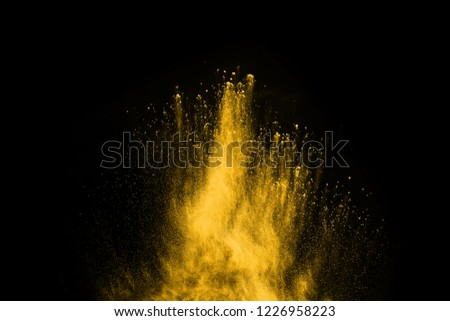 Freeze motion of yellow dust explosion isolated on black background #1226958223