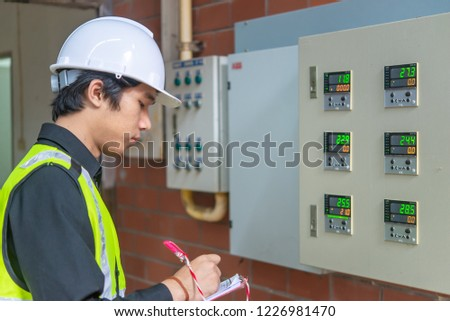 Asian Maintenance engineer at the waste water management system of a huge factory,maintenance checking technical data of heating system equipment,Thailand people #1226981470