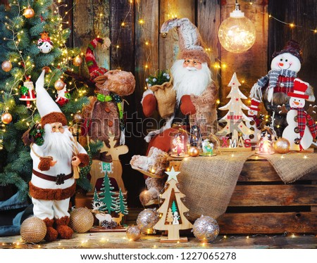 Santa Claus  dolls and christmas decorations on dark rustic wooden backgroud with light garland. #1227065278