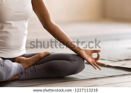 Yogi black woman practicing yoga lesson, breathing, meditating, doing Ardha Padmasana exercise, Half Lotus pose with mudra gesture, working out, indoor close up. Well being, wellness concept #1227113218