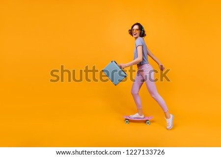 Active caucasian woman with valise skating in studio. Indoor shot of magnificent curly girl standing on longboard on yellow background. #1227133726
