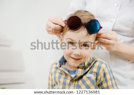 Little cute cunning blonde boy with big blue eyes wearing glasses colored lenses on his forehead. Doctor ophthalmologist holds them hands #1227136081