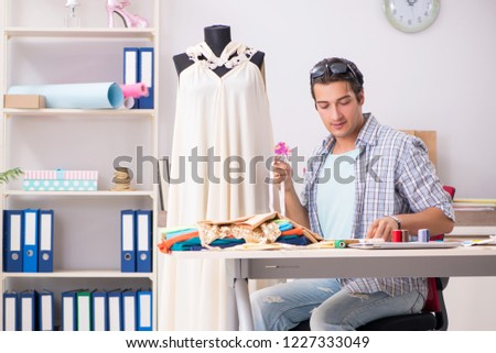 Young handsome tailor working in his workshop #1227333049