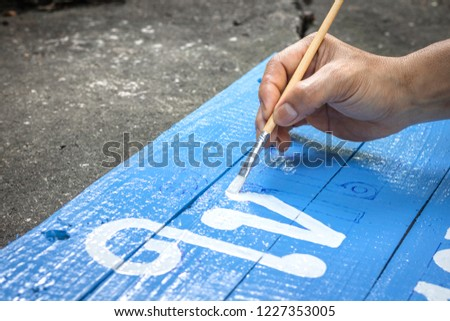 A hand writing signs board with a brush of watercolors on cement floor background. Painting on wooden board in thai language for advertising.