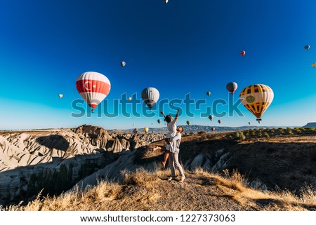 Couple in love among balloons. A guy proposes to a girl. Couple in love in Cappadocia. Couple in Turkey. Honeymoon in the mountains. Man and woman traveling. Flying on balloons. Wedding. Journey. Love #1227373063