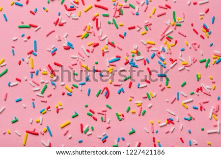 trendy pattern of colorful sprinkles over pink background, decoration for cake and bakery Royalty-Free Stock Photo #1227421186