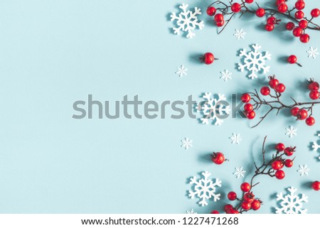 Christmas or winter composition. Frame made of snowflakes and red berries on pastel blue background. Christmas, winter, new year concept. Flat lay, top view, copy space #1227471268