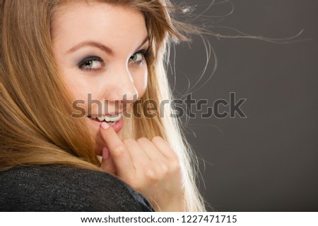 Haircare, beauty, hairstyling concept. Portrait of charming young attractive blonde flirting woman wearing dark t shirt having windblown beautiful long hair. #1227471715