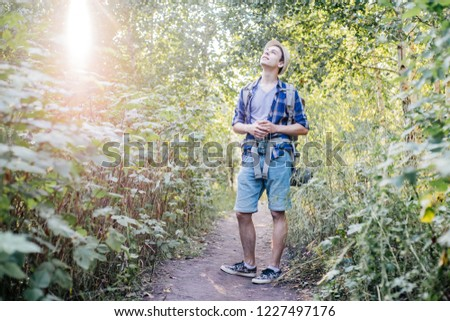young traveler guy hiking with backpack in the nature #1227497176