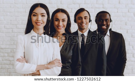 Young Smiling Managers Standing in Modern Office. Training in Office. Modern Office Concept. Smiling Worker. Standing in Room. Woman in White Shirt. Man in Black Suit. White Wall in Office. #1227502612
