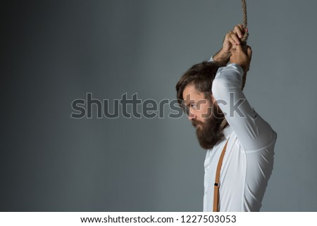 Young handsome man with a beard in a white shirt and yellow suspenders on gallows on a gray background #1227503053